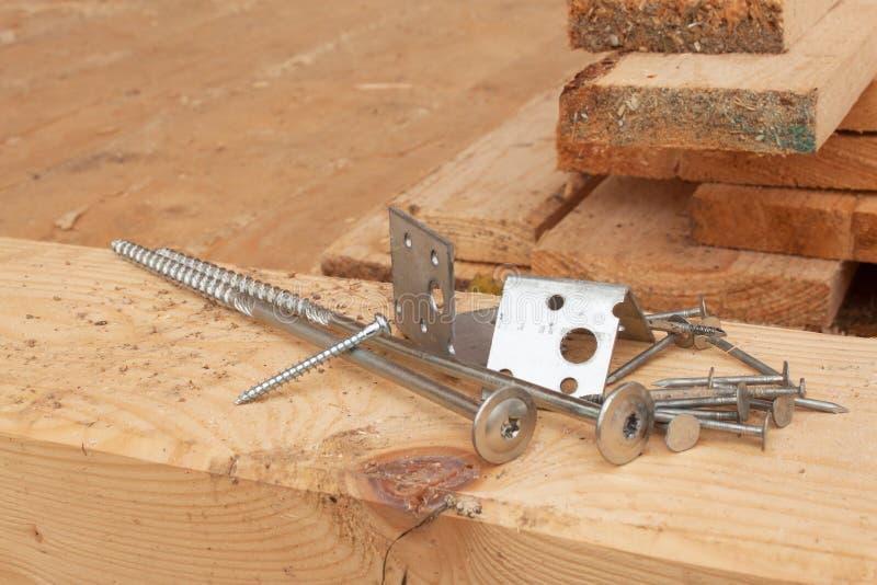 Βίδες και καρφιά για να χτίσει ένα ξύλινο σπίτι Ενώνοντας ξύλινες ακτίνες Οικοδομές στοκ φωτογραφία με δικαίωμα ελεύθερης χρήσης