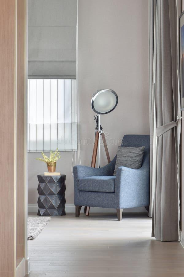 Βαθιά μπλε πολυθρόνα με το μοντέρνο μόνιμο λαμπτήρα στη γωνία του καθιστικού στο σπίτι στοκ εικόνες