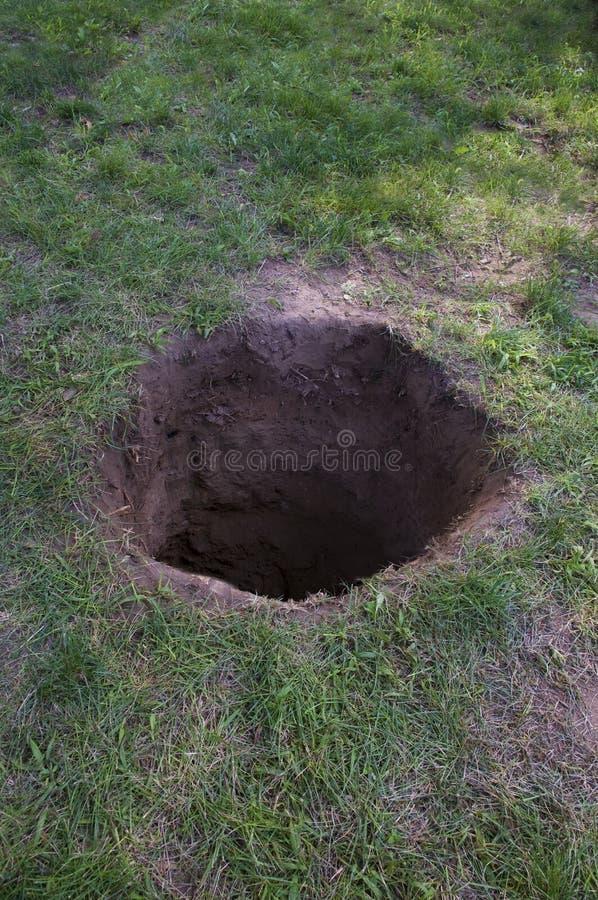 Βαθιά τρύπα ρύπου στο έδαφος στοκ εικόνα