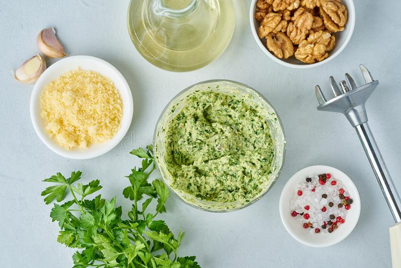 Βαθμιαία συνταγή Ζυμαρικά Pesto, bavette με τα ξύλα καρυδιάς, μαϊντανός, σκόρδο, καρύδια, ελαιόλαδο Τοπ άποψη, μπλε υπόβαθρο στοκ φωτογραφίες
