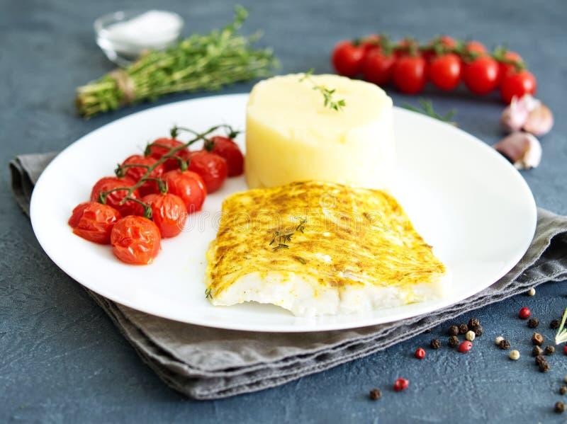 Βακαλάος ψαριών που ψήνεται στο φούρνο με τις πολτοποιηίδες πατάτες, ντομάτες, υγιή τρόφιμα διατροφής Σκούρο γκρι υπόβαθρο, πλάγι στοκ φωτογραφία