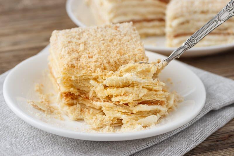 Βαλμένο σε στρώσεις κέικ με τη φέτα βανίλιας Napoleon κρέμας millefeuille σε ένα άσπρο πιάτο στοκ εικόνα