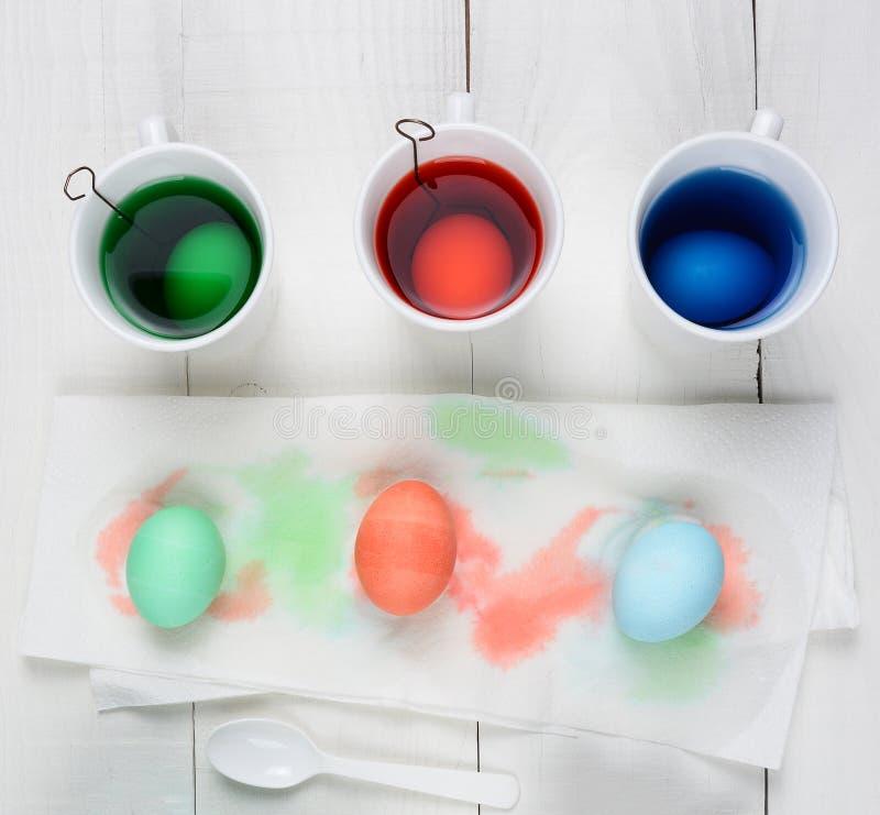 Βαμμένα αυγά που ξεραίνουν σε μια πετσέτα εγγράφου με τρία φλυτζάνια της χρωστικής ουσίας σε έναν αγροτικό ξύλινο πίνακα στοκ εικόνες με δικαίωμα ελεύθερης χρήσης