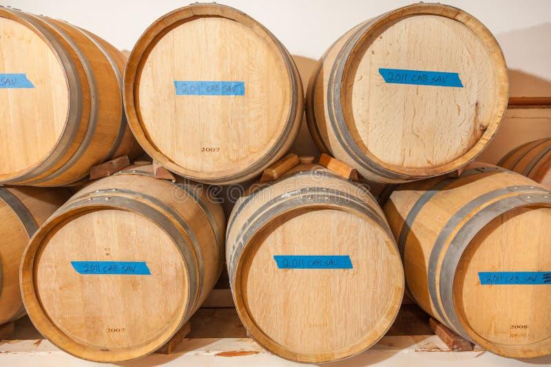 Βαρέλια κρασιού και ηλικία μπουκαλιών μέσα στο σκοτεινό κελάρι στοκ φωτογραφίες