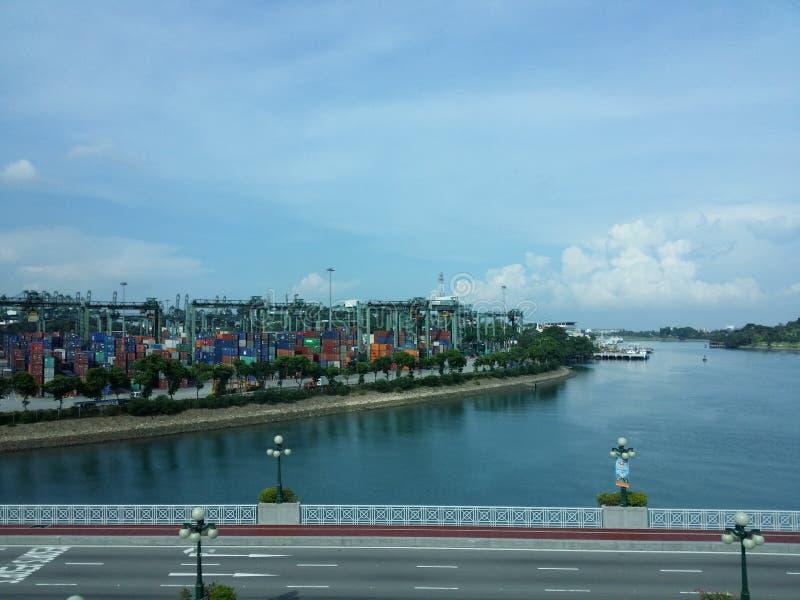 Βαριά εμπορευματοκιβώτια που φορτώνουν με την ειρηνική άποψη παραλίας στοκ εικόνα