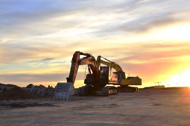 Βαριοί ακολουθημένοι εκσκαφείς σε ένα εργοτάξιο οικοδομής σε ένα ηλιοβασίλεμα υποβάθρου στοκ εικόνα