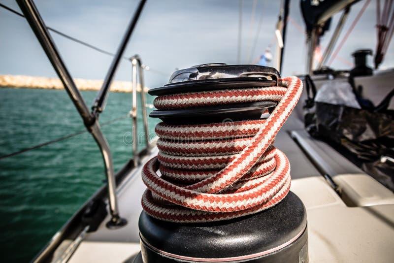 Βαρούλκο με το κόκκινο και άσπρο σχοινί στην πλέοντας βάρκα στη θάλασσα στοκ εικόνα με δικαίωμα ελεύθερης χρήσης