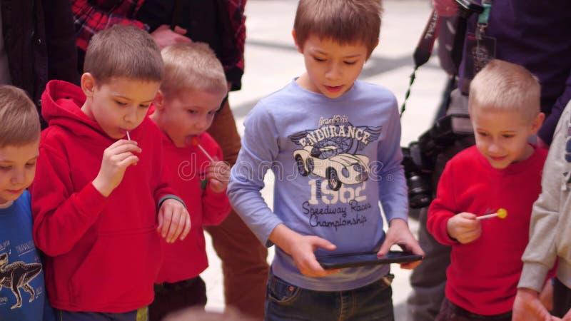 ΒΑΡΣΟΒΙΑ, ΠΟΛΩΝΙΑΣ - 4 ΜΑΡΤΙΟΥ, 2017 Μικρά παιδιά που ενεργοποιούν ενθουσιωδώς τα μικρά ρομπότ που χρησιμοποιούν τον υπολογιστή τ στοκ εικόνες