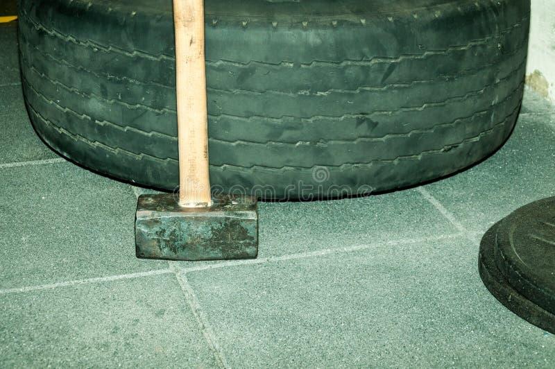 Βαρύ hummer με την ξύλινη λαβή που κλίνει στη μεγάλη ρόδα φορτηγών για τη σκληροπυρηνική κατάρτιση δύναμης στη γυμναστική στοκ εικόνες