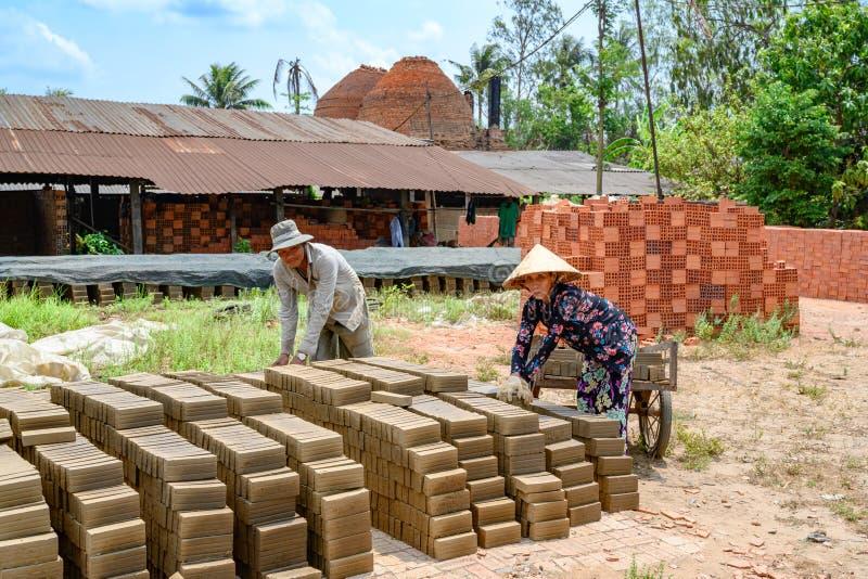 Βασικά χειροποίητα τούβλα ανδρών και γυναικών κοντά στο ποταμό Μεκόνγκ, Βιετνάμ στοκ εικόνα με δικαίωμα ελεύθερης χρήσης