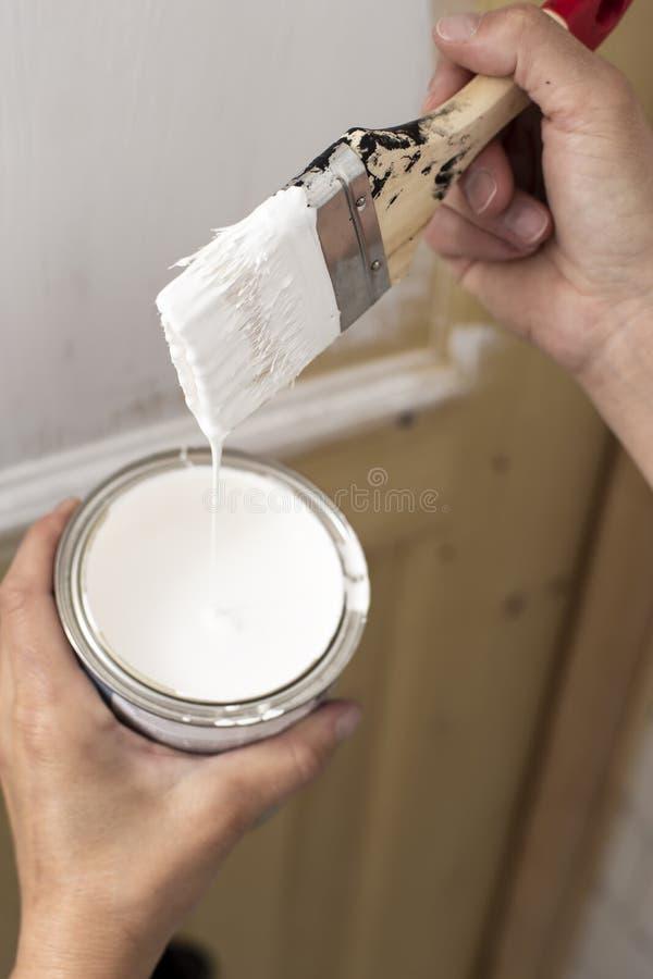 βασικές επισκευές Το ανθρώπινο χέρι που κρατά το α μπορεί άσπρου να χρωματίσει και μιας βούρτσας στη nedokrashennoy ξύλινη πόρτα  στοκ φωτογραφίες