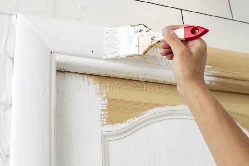 βασικές επισκευές Το χέρι με μια βούρτσα χρωματίζει ένα ξύλινο πλαίσιο πορτών στο άσπρο χρώμα στο λουτρό στοκ εικόνα με δικαίωμα ελεύθερης χρήσης