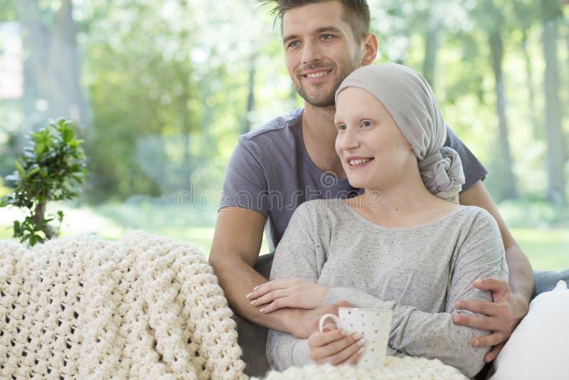 βασικό χαμόγελο ζευγών Σύζυγος που υποστηρίζει την άρρωστη σύζυγο μετά από το chemo στοκ φωτογραφία