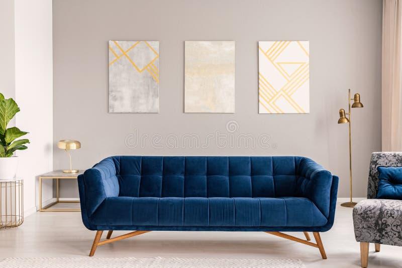 Βασιλικός μπλε καναπές που στέκεται στην πραγματική φωτογραφία του ανοικτό γκρι εσωτερικού καθιστικών με χρυσούς λαμπτήρες και τρ στοκ εικόνες