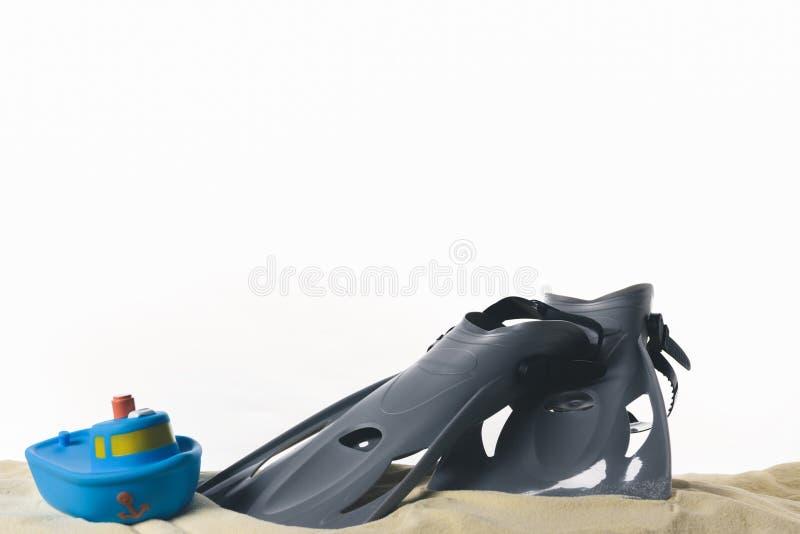 Βατραχοπέδιλα και βάρκα παιχνιδιών στην άμμο στοκ εικόνα με δικαίωμα ελεύθερης χρήσης