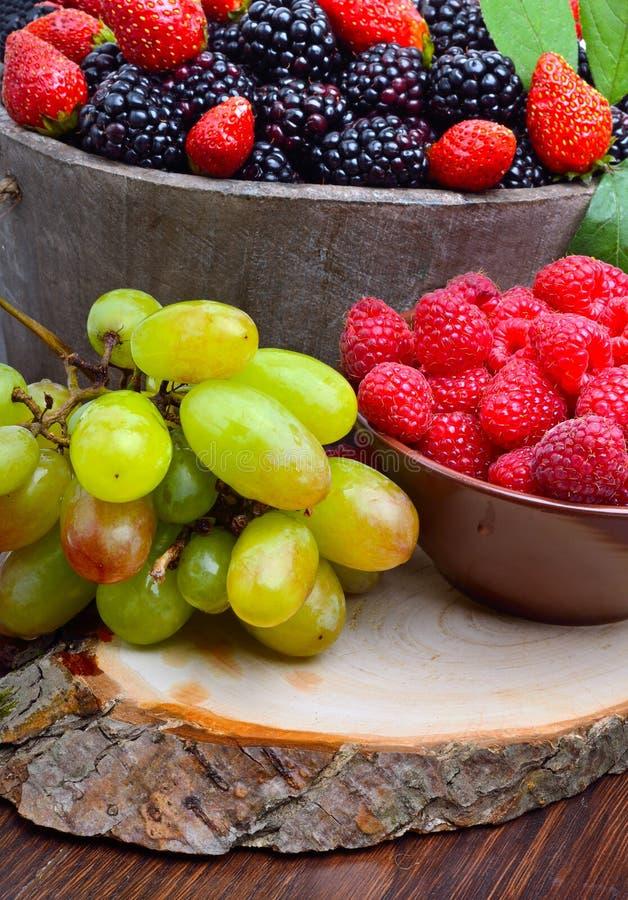 Download Βατόμουρα, φράουλα, σμέουρο και σταφύλια σε έναν ξύλινο Στοκ Εικόνες - εικόνα από φυσικός, σφαιριστών: 62701042