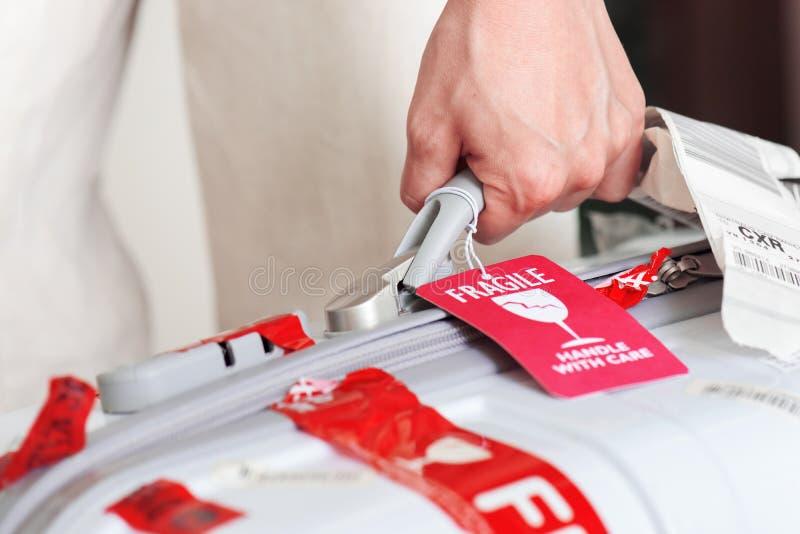 Βαλίτσα εκμετάλλευσης ατόμων με την ετικέττα αποσκευών υπό εξέταση στον αερολιμένα στοκ φωτογραφία με δικαίωμα ελεύθερης χρήσης