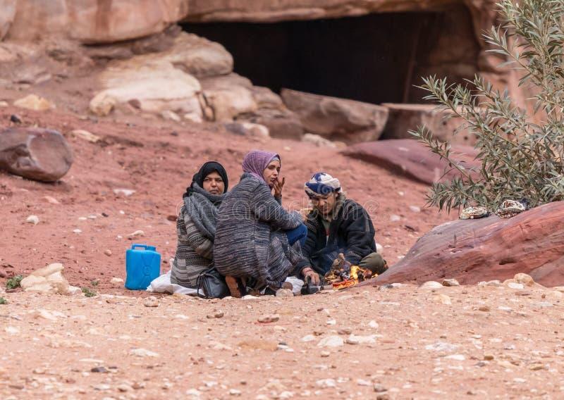 Βεδουίνη οικογενειακή συνεδρίαση στο έδαφος και κατανάλωση των τροφίμων στο πόδι του κόκκινου βράχου στη Petra κοντά στην πόλη Wa στοκ φωτογραφίες με δικαίωμα ελεύθερης χρήσης