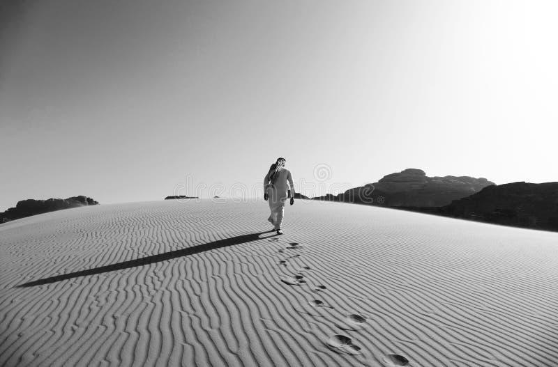 Βεδουίνο περπάτημα στους αμμόλοφους άμμου στην έρημο ρουμιού Wadi, Ιορδανία σε γραπτό στοκ εικόνες