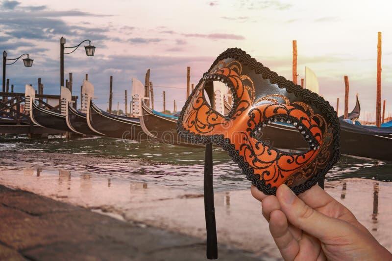 Βενετική μάσκα καρναβαλιού στο παραδοσιακό βενετσιάνικο φεστιβάλ στην Ιταλία Πολλές γόνδολες στο παρασκήνιο στοκ εικόνα με δικαίωμα ελεύθερης χρήσης