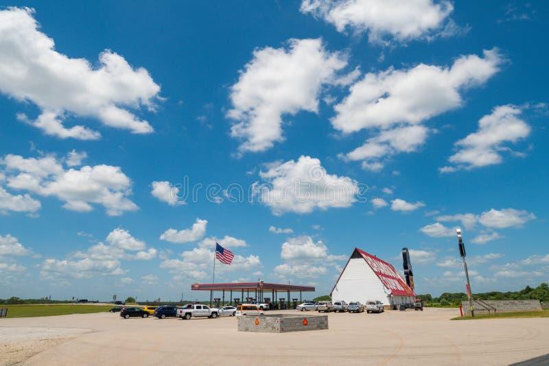 Βενζινάδικο στις ΗΠΑ με τα μέρη του ευρύ ανοιχτού χώρου και της αμερικανικής σημαίας που φυσούν στον αέρα στοκ εικόνες