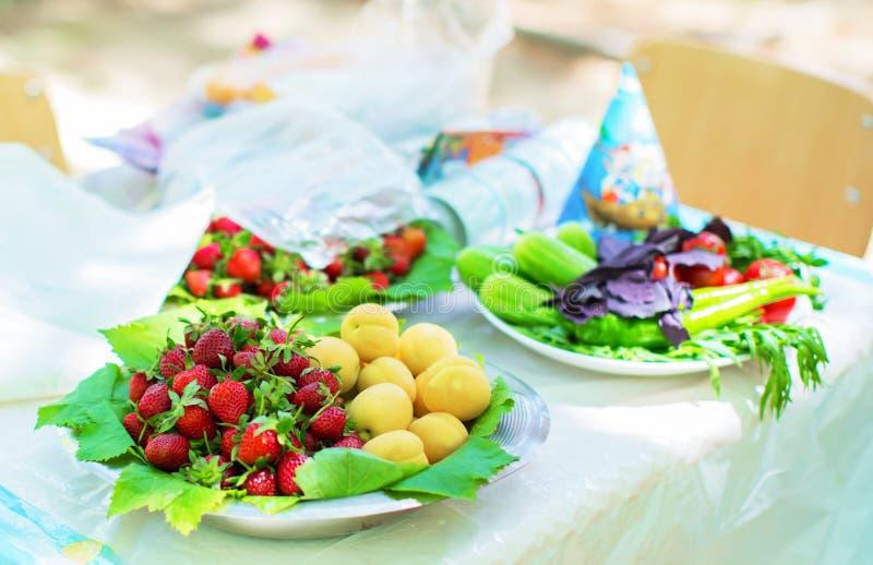 Βερίκοκα και φράουλες στους νωπούς καρπούς κύπελλων στοκ εικόνα