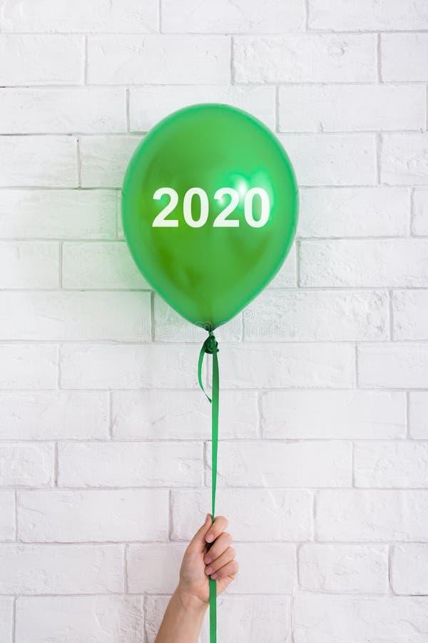 Βεραμάν μπαλόνι με την έννοια του 2020 στο χέρι γυναικών στο λευκό στοκ φωτογραφία με δικαίωμα ελεύθερης χρήσης
