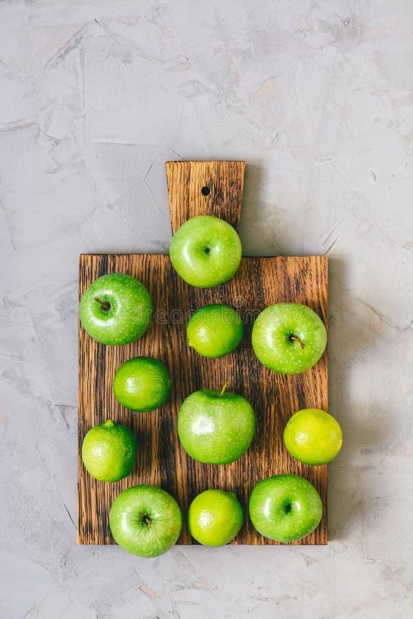 Βεραμάν φρούτα και μήλα ασβέστη Οι νωποί καρποί εξυπηρετούνται σε έναν τέμνοντα πίνακα σε ένα γκρίζο συγκεκριμένο υπόβαθρο στοκ φωτογραφία