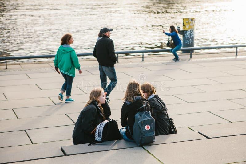 Βερολίνο, στις 3 Οκτωβρίου 2017: Μια ομάδα φίλων νέων κοριτσιών των σπουδαστών που κάθονται στην προκυμαία που βρίσκεται κοντά στοκ εικόνες