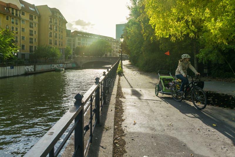 ΒΕΡΟΛΙΝΟ, ΓΕΡΜΑΝΙΑ - 28 Ιουλίου 2018: Από το Βερολίνο mom ποδηλατών που οδηγά ένα ποδήλατο στο για τους πεζούς πέρασμα του καναλι στοκ φωτογραφία με δικαίωμα ελεύθερης χρήσης