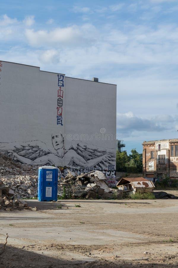 ΒΕΡΟΛΙΝΟ, ΓΕΡΜΑΝΙΑ - 28 Ιουλίου 2018: Προοπτική μιας ζωγραφικής αγγέλου στον άσπρο τοίχο πίσω από πολλά συντρίμμια κατασκευής, α στοκ φωτογραφία με δικαίωμα ελεύθερης χρήσης
