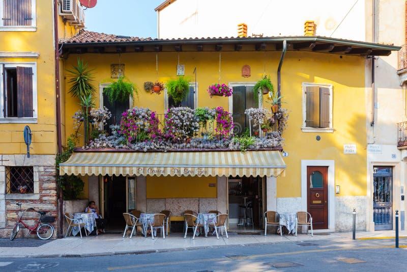 ΒΕΡΟΝΑ, ΙΤΑΛΙΑ 8 Σεπτεμβρίου 2016: Μικρός καφές στο παλαιό διώροφο σπίτι με το όμορφο μπαλκόνι με τα λουλούδια που βρίσκεται σε P στοκ εικόνα με δικαίωμα ελεύθερης χρήσης
