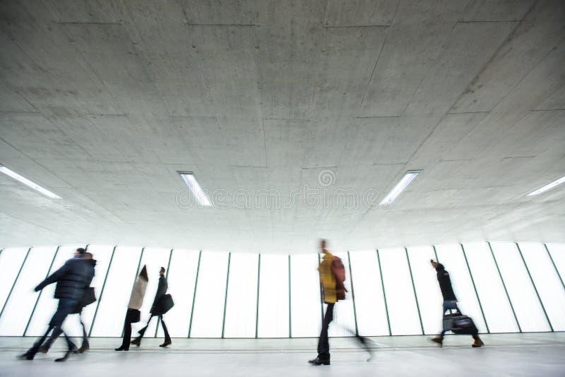 Βιασύνη αερολιμένων: άνθρωποι με τις βαλίτσες τους που περπατούν κατά μήκος ενός corrid στοκ εικόνες