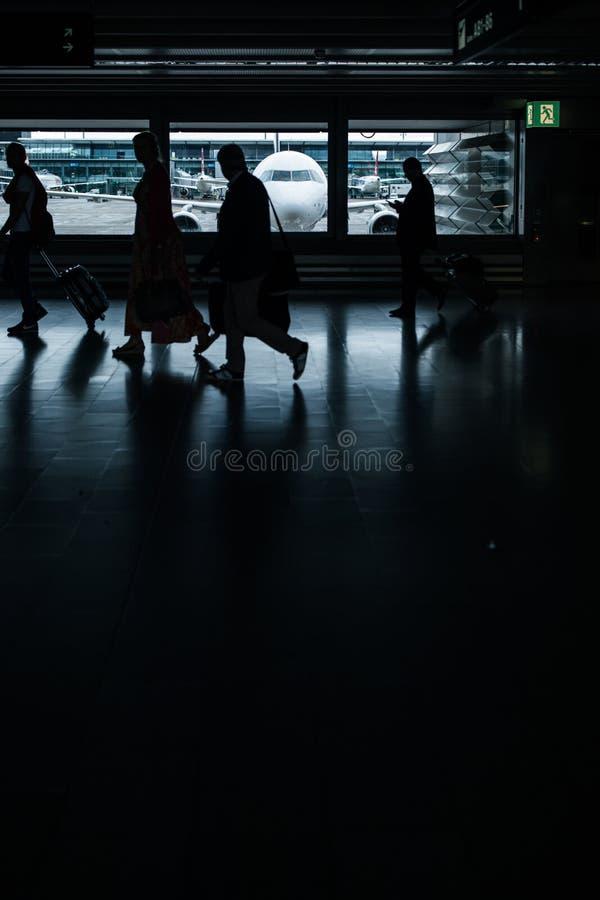 Βιασύνη αερολιμένων: άνθρωποι με τις βαλίτσες τους που περπατούν κατά μήκος ενός διαδρόμου στοκ εικόνα με δικαίωμα ελεύθερης χρήσης