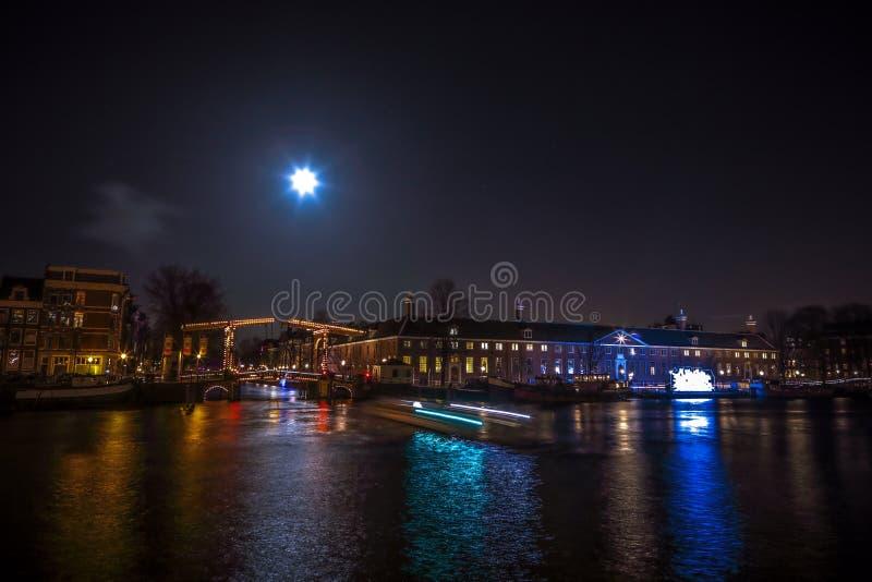 Βιασύνη βαρκών κρουαζιέρας στα κανάλια νύχτας Ελαφριές εγκαταστάσεις στα κανάλια νύχτας του Άμστερνταμ μέσα στο ελαφρύ φεστιβάλ στοκ φωτογραφία