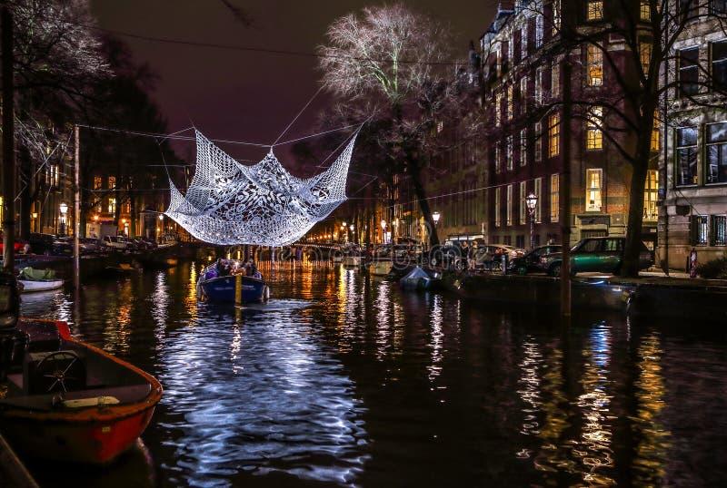 Βιασύνη βαρκών κρουαζιέρας στα κανάλια νύχτας Ελαφριές εγκαταστάσεις στα κανάλια νύχτας του Άμστερνταμ μέσα στο ελαφρύ φεστιβάλ στοκ φωτογραφίες