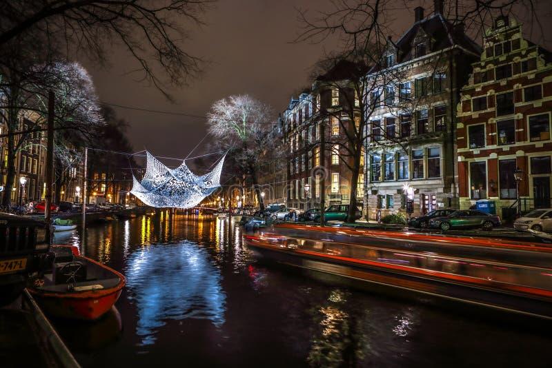 Βιασύνη βαρκών κρουαζιέρας στα κανάλια νύχτας Ελαφριές εγκαταστάσεις στα κανάλια νύχτας του Άμστερνταμ μέσα στο ελαφρύ φεστιβάλ στοκ φωτογραφία με δικαίωμα ελεύθερης χρήσης