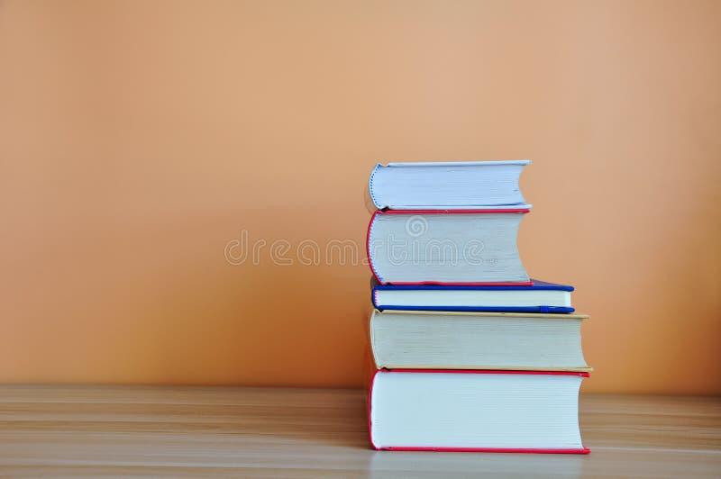 Βιβλία βιβλίων με σκληρό εξώφυλλο στον ξύλινο πίνακα με το κίτρινο υπόβαθρο στοκ εικόνες