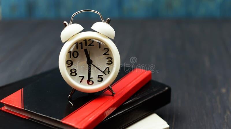 Βιβλία και λευκό ρολογιών συναγερμών ρολογιών σε ένα ξύλινο μπλε υπόβαθρο ι στοκ φωτογραφία με δικαίωμα ελεύθερης χρήσης