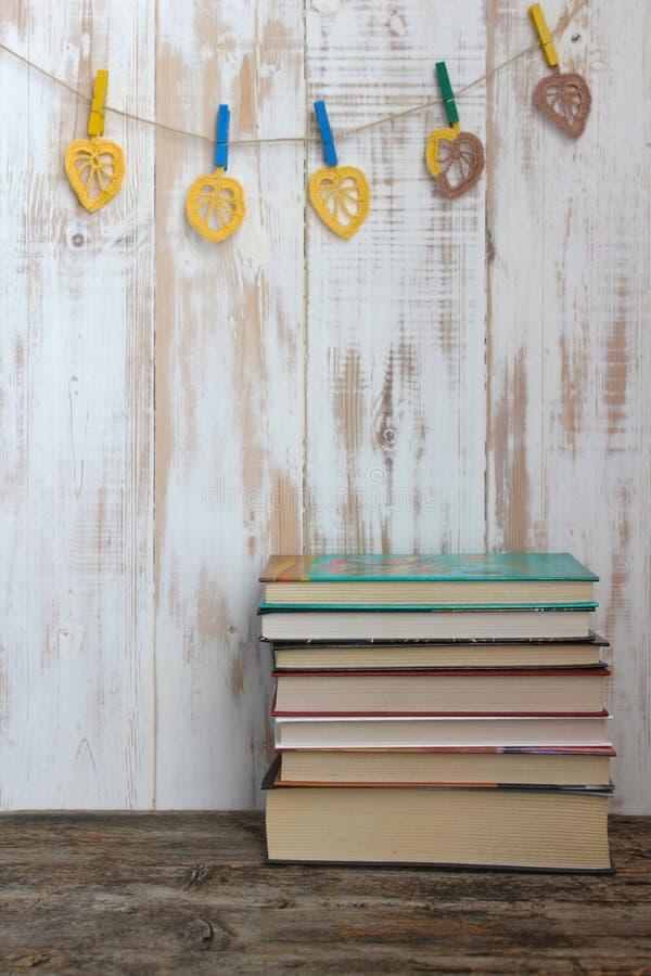 Βιβλία και πλεγμένα χειροποίητα φύλλα στο εκλεκτής ποιότητας άσπρο ξύλινο υπόβαθρο στοκ φωτογραφίες