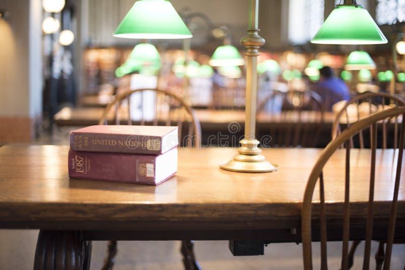 Βιβλία στον πίνακα στη βιβλιοθήκη στοκ φωτογραφία