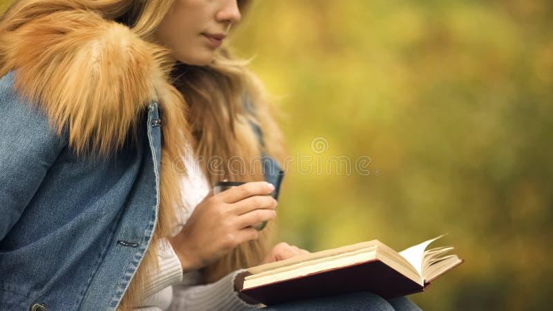 Βιβλίο ανάγνωσης γυναικών και τσάι κατανάλωσης στο κατώφλι, που απολαμβάνει τον καιρό πτώσης, ευχαρίστηση στοκ εικόνα με δικαίωμα ελεύθερης χρήσης