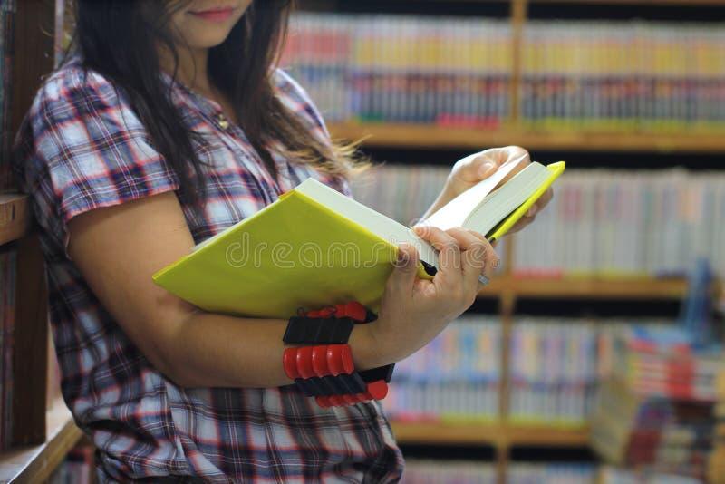 Βιβλίο ανάγνωσης γυναικών στο δωμάτιο βιβλιοθηκών και το υπόβαθρο ραφιών, έννοια εκπαίδευσης στοκ φωτογραφίες με δικαίωμα ελεύθερης χρήσης