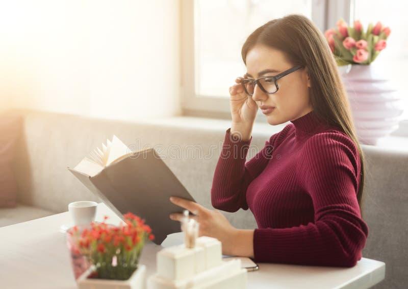 Βιβλίο ανάγνωσης κοριτσιών στον καφέ στοκ φωτογραφίες με δικαίωμα ελεύθερης χρήσης