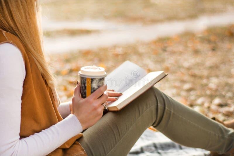 Βιβλίο ανάγνωσης κοριτσιών στο φλιτζάνι του καφέ πάρκων και εκμετάλλευσης στοκ φωτογραφία