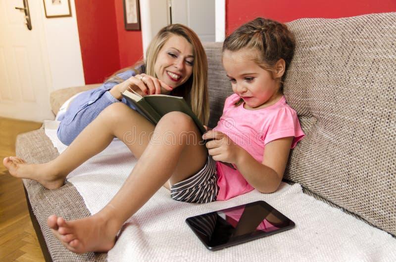 Βιβλίο ανάγνωσης μικρών κοριτσιών στη μητέρα της στοκ εικόνα με δικαίωμα ελεύθερης χρήσης