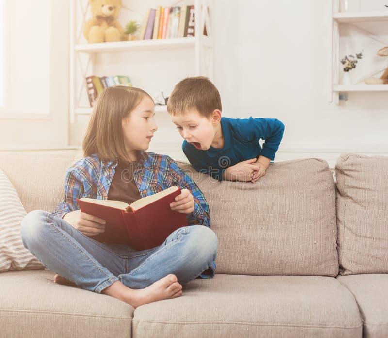 Βιβλίο ανάγνωσης νέων κοριτσιών για τον αδελφό της στοκ φωτογραφία με δικαίωμα ελεύθερης χρήσης