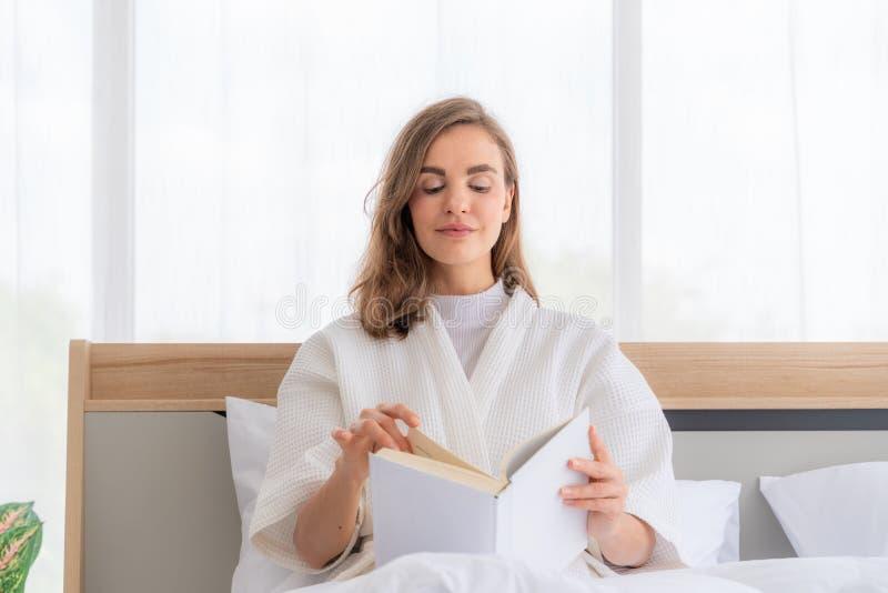 Βιβλίο ανάγνωσης στο κρεβάτι Θηλυκό βιβλίο ανάγνωσης προσώπων στο κρεβάτι το πρωί στοκ εικόνα με δικαίωμα ελεύθερης χρήσης