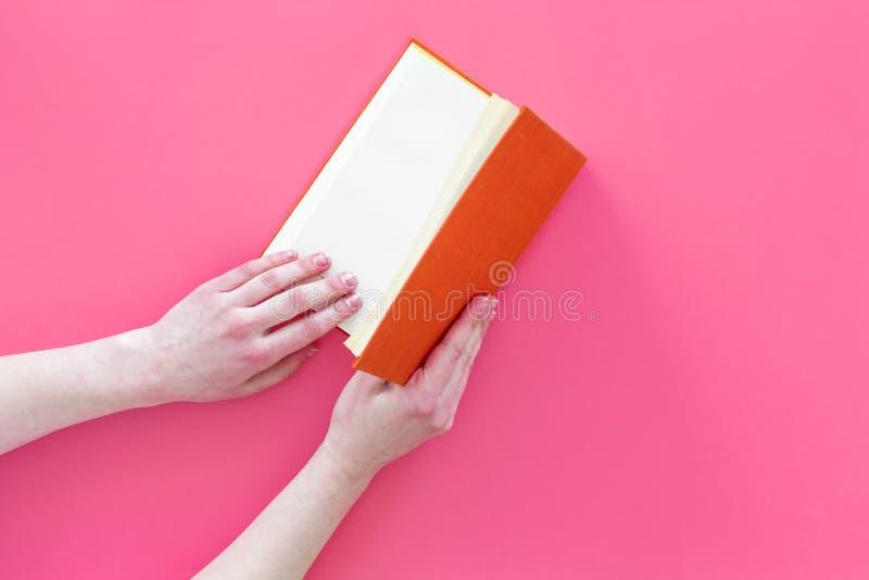 βιβλίο ανοικτό Βιβλίο βιβλίων με σκληρό εξώφυλλο λαβής χεριών που ανοίγουν στο ρόδινο διάστημα αντιγράφων άποψης υποβάθρου τοπ στοκ εικόνες