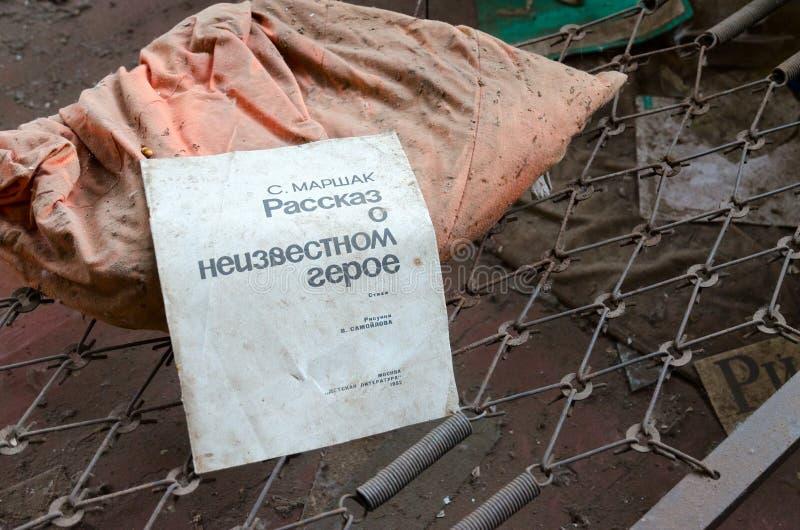 Βιβλίο στο πλέγμα μετάλλων του κρεβατιού στον εγκαταλειμμένο παιδικό σταθμό στο χωριό της ζώνης αποκλεισμού Kopachi του πυρηνικού στοκ φωτογραφία